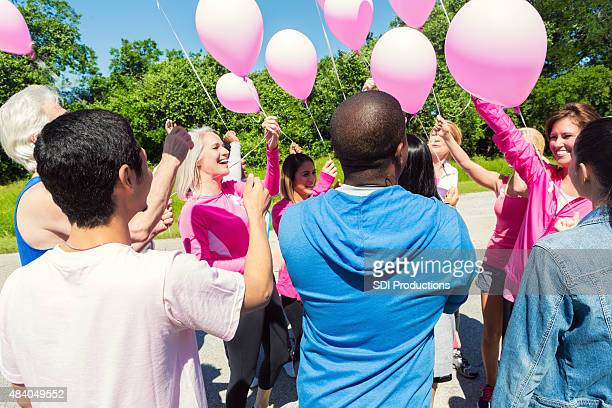 Group of adults releasing pink balloons for breast cancer charity