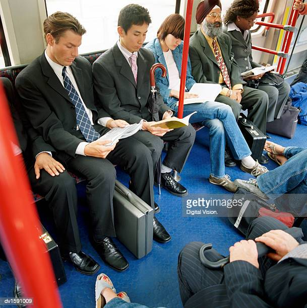 Group of Adults Sit Next to Each Other on a Passenger Train