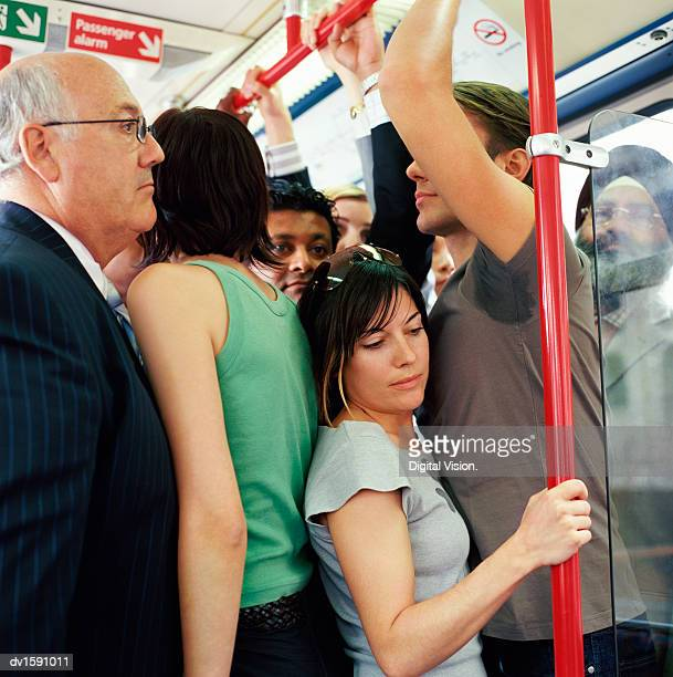 group of adults stands uncomfortably crowded onto a passenger train - affollato foto e immagini stock