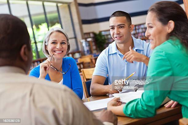 Group of adults studying together in library continuing education
