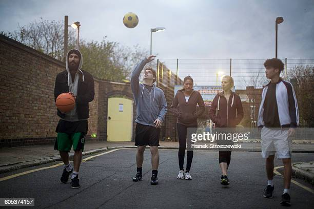Group of adults walking in road, holding basketball and football