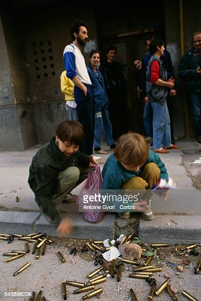 A group of adults watches two Bosnian boys collect machine gun cartridge casings in the streets of Sarajevo while the city is besieged during the...