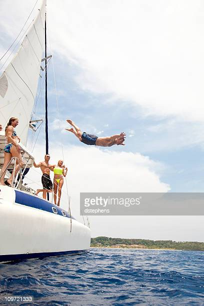 group of adults watching friend jump into caribbean sea - catamaran stock photos and pictures