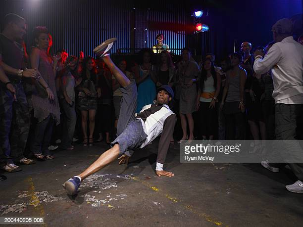 Group of adults watching man breakdance in club, DJ in background