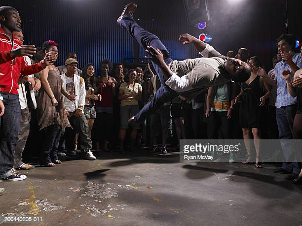 Group of adults watching man breakdance in club
