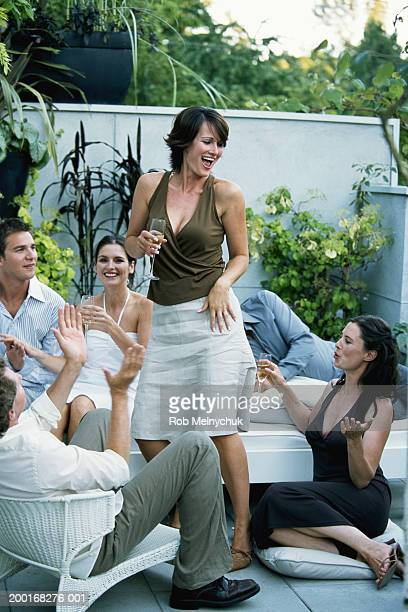 Group of adults watching woman dance at cocktail party, smiling