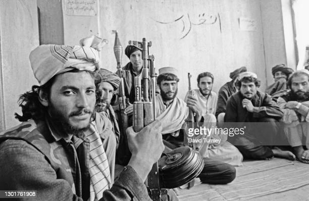 Group of Afghan man wearing lungee turbans and pakols, with AK-47 assault rifles, and one with a rocket-propelled grenade launcher, in Afghanistan,...