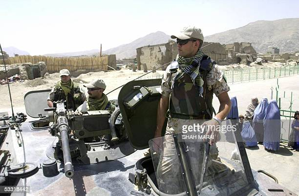 A group of Afghan women watch Italian soldiers of the International Security Assistance Force patrol the streets of Kabul 03 August 2005 Austria was...