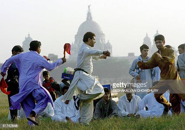 A group of Afghans residing in India perform a traditional dance at a ground in front of the Victoria Memorial in Calcutta 15 November 2004 as they...