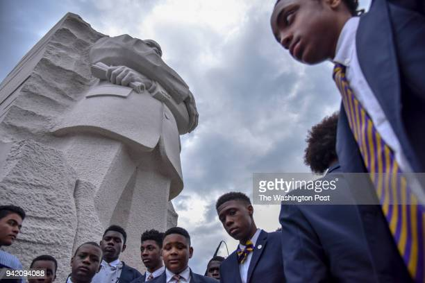 A group of African American young men gather at the foot of the DC memorial of Reverend Dr Martin Luther King Jr following a ceremonial wreath laying...