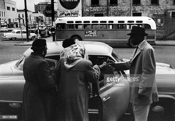 A group of African Americans get into an automoboile to car pool during the Montgomery bus boycott Montgomery Alabama February 1956 An empty city bus...