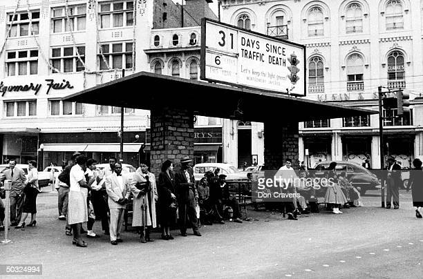 Group of African Americans including American civil rights activist, Rosa Parks waiting at a busy bus stop following a Supreme Court ruling ending...