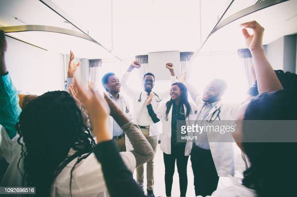 group of african medical students celebrating and laughing spontaneously together - medical student stock pictures, royalty-free photos & images