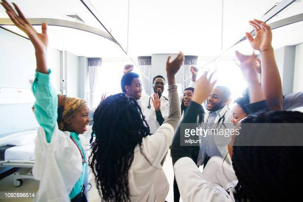 group of african medical students celebrating success spontaneously together - junior doctor stock pictures, royalty-free photos & images