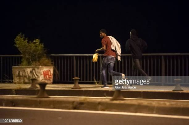 Group of African migrants headed to France to cross the Spanish-French border walk along Santiago bridge on August 22, 2018 in Irun, Spain. Migrants...