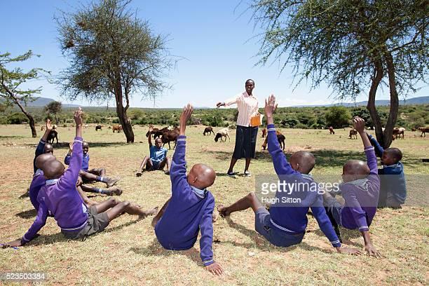group of african schoolboys (10-12) with teacher during outdoor lesson - hugh sitton stockfoto's en -beelden