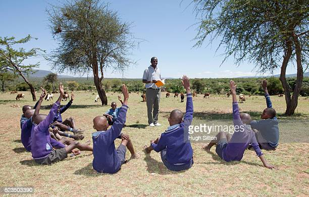 group of african schoolboys (10-12) with teacher during outdoor lesson - hugh sitton stock pictures, royalty-free photos & images