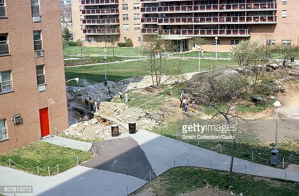 A group of AfricanAmerican and Caucasian youth gather among debris on the lawn of a housing project in the Bronx New York City New York 1976