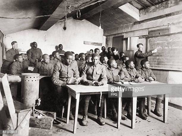 A group of AfricanAmerican soldiers in a schoolroom at Commercy Post a military camp in northeastern France circa 1918 Part of the text on the...