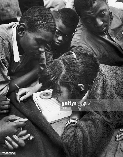 A group of AfricanAmerican teenagers listening to a transistor radio circa 1960