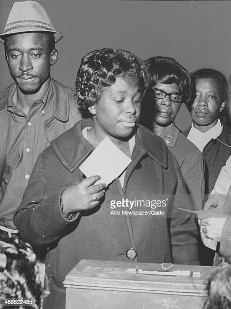 A group of AfricanAmerican voters stand in line while a woman places her ballot into a ballot box Baltimore Maryland November 10 1964