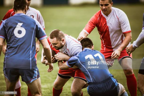 group of aggressive sportsmen playing rugby match on a stadium. - rugby union stock pictures, royalty-free photos & images