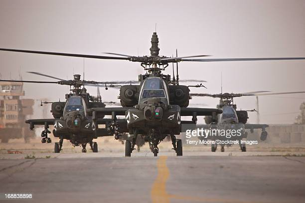 A group of AH-64D Apache helicopters on the runway at COB Speicher.