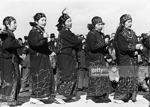 A group of Ainu women perform a traditional dance All the women have tattooed lips a ritual which is carried out during childhood The tribe have no...