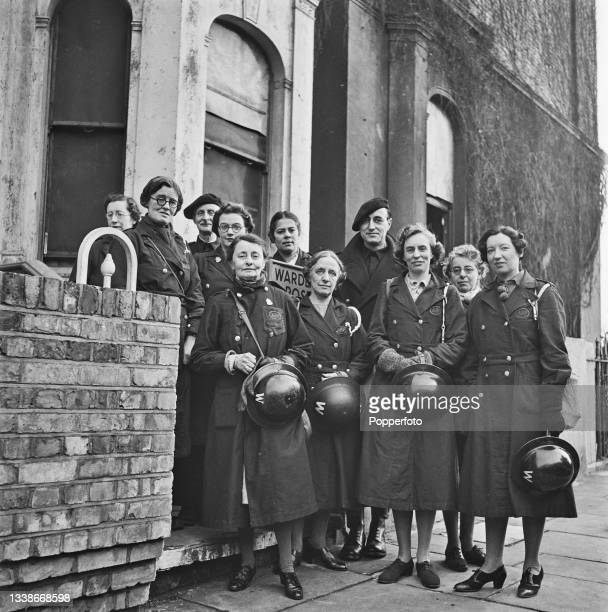 Group of Air Raid Precautions wardens posed together on a street in Kensington, London during World War II on 13th January 1942.