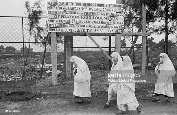 A group of Algerian women wearing chadors walk past a sign written in French