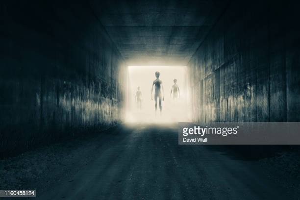 a group of aliens emerging from the light at the end of a dark sinister tunnel. with a high contrast edit. - alien stock pictures, royalty-free photos & images