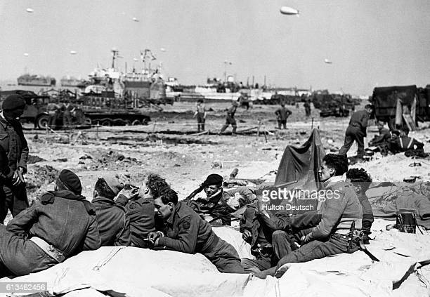 A group of Allied forces commandos rest on one of the Normandy landing beaches and watch equipment being unloaded from some of the landing craft The...