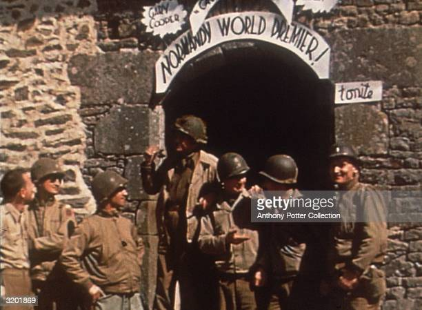Group of Allied soldiers relax in front of a stone archway, the entrance to a makeshift cinema where a Gary Cooper film is playing, in the Normandy...