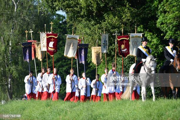 A group of altar servers walks on a gravel path during the traditional Blood Ride in Weingarten Germany 26 May 2017 Various horseman wearing top hats...