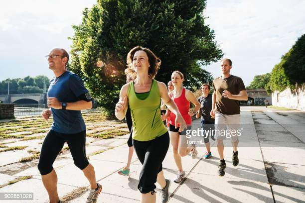 group of amateur athletes training together outdoors in city sun - amateur stock pictures, royalty-free photos & images