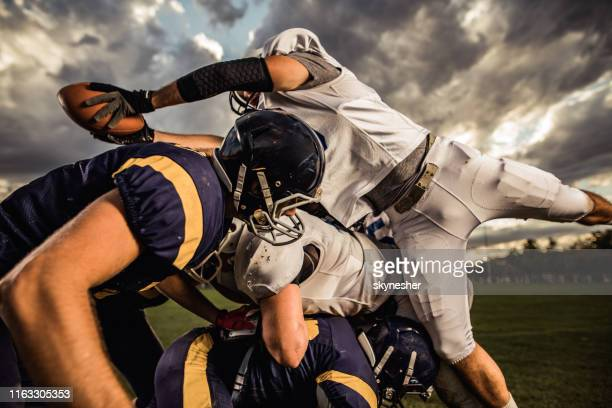 group of american football players on a pile during a match on playing field. - touchdown stock pictures, royalty-free photos & images