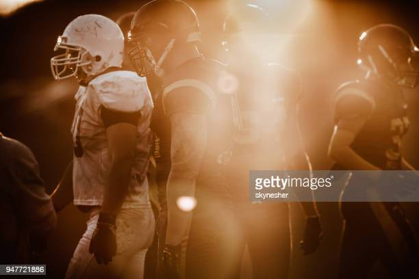 group of american football players walking on the field. - american football team stock pictures, royalty-free photos & images