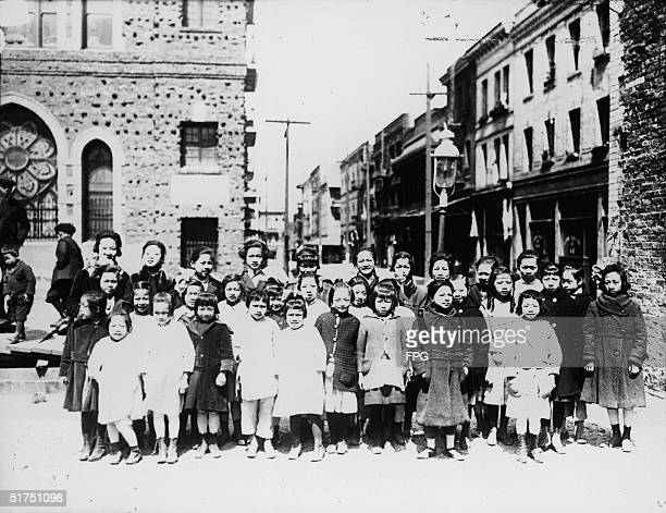 A group of American school children wear Winter coats as they pose for a class photograph outside their school in Chinatown San Francisco early 20th...