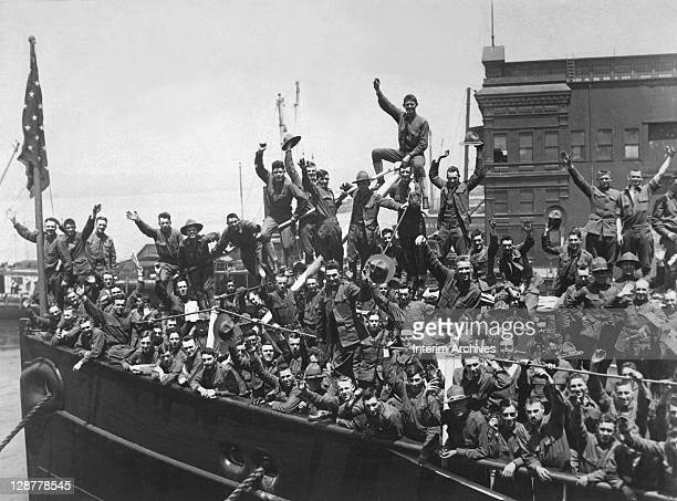 A group of American soldiers wave heartily from the deck of a ship transporting them to the fighting in France during World War I 1917