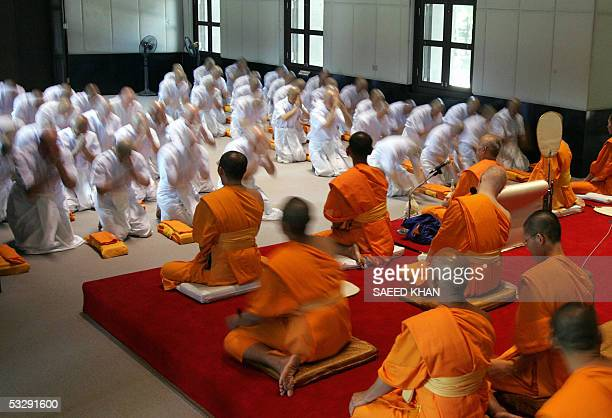 STORY AFPLIFESTYLETHAILANDBRITAINBUDDHISM A group of Americans and Europeans bow down during an ordination ceremony in a traditional Thai chapel at...