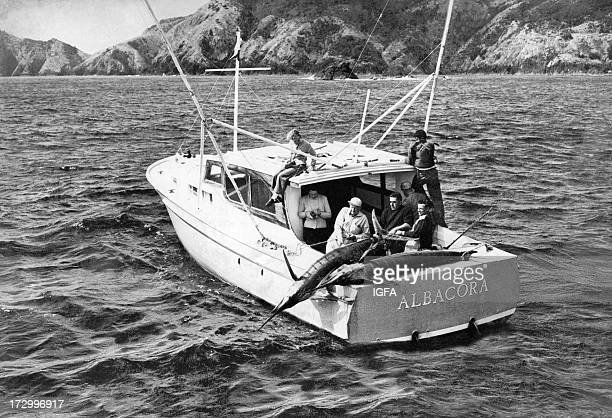 A group of anglers and two marlin are on the Albacora fishing boat in waters off the New Zealand coast circa 1950