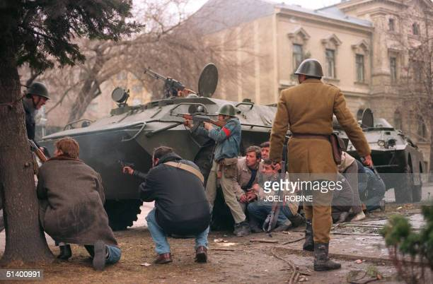 A group of antiCommunist civilian fighters along with a Romanian soldier supporting antiCeausescu's activists protect themselves behind an armoured...