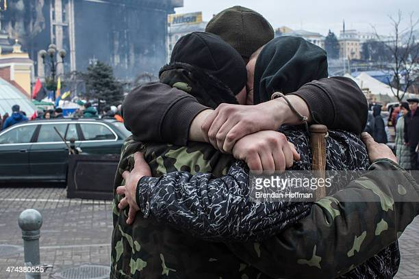 A group of antigovernment protesters share a hug on Independence Square on February 23 2014 in Kiev Ukraine After a chaotic and violent week Viktor...