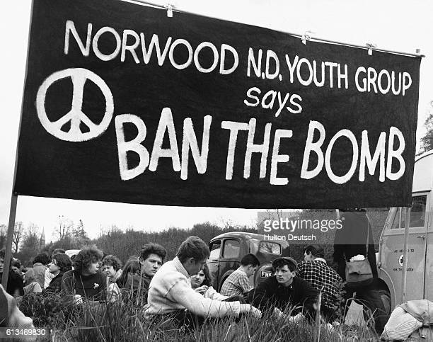 A group of antinuclear weapons protesters sit beneath a 'ban the bomb' banner at a protest