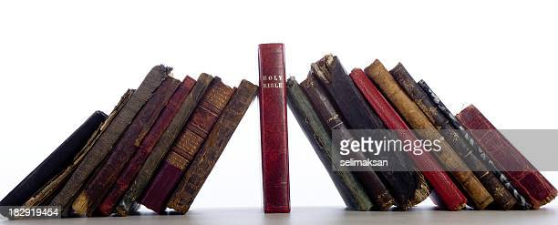 Group Of Antique Old Books Leaning On Bible As Keystone