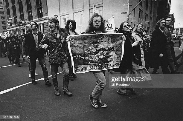 A group of antiVietnam War protestors carry a poster showing the 'My Lai Massacre' during the 'Home With Honor' parade to mark the homecoming of...