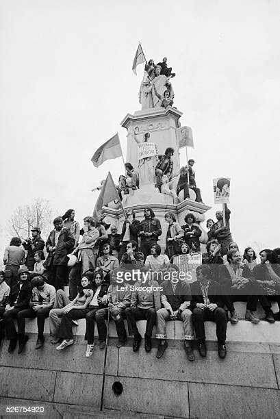 A group of antiwar protesters sit on the America Weeping on the Shoulders of History statue in front of the Capitol during a protest for the students...