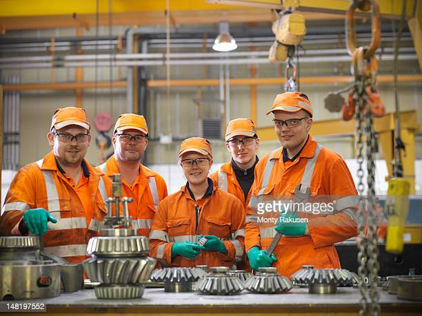 Group of apprentice engineers and engineer inspecting gears