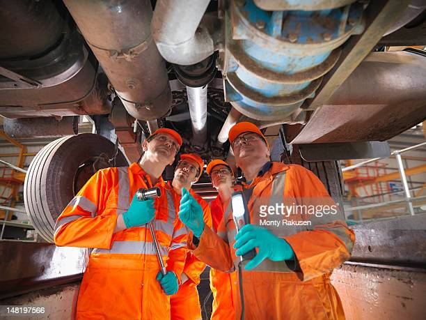 Group of apprentice engineers and engineer inspecting underneath truck