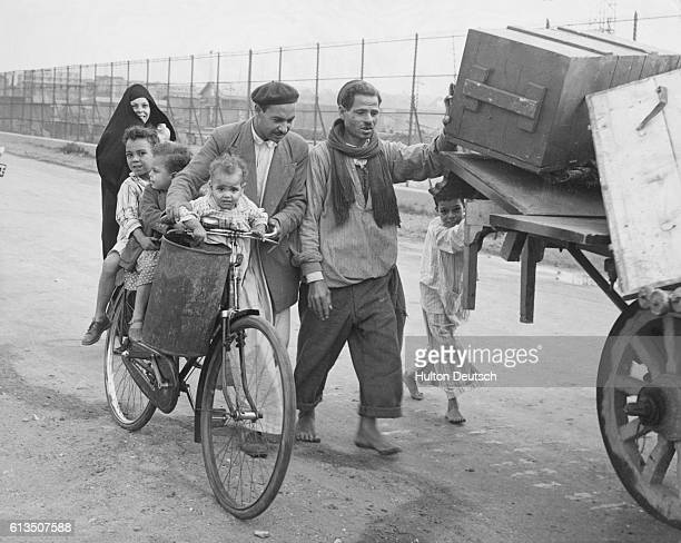 A group of Arabs leave Port Said after British and French troops move into the area during the Suez Crisis of 1956